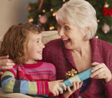 Девочка дарит бабушке подарок на Новый год